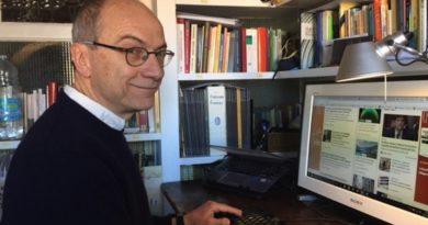 Il giornalista ambientale Antonio Cianciullo seduto alla sua scrivania, con il computer davanti e la libreria sullo sfondo