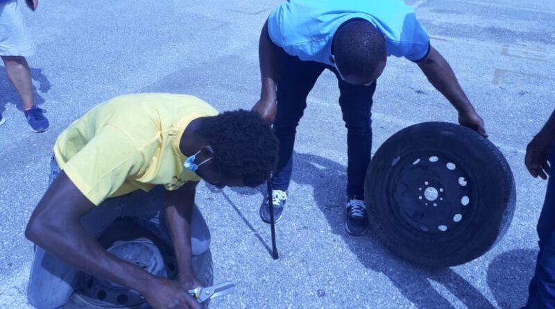 Due ragazzi della Cooperativa Sociale Ethica di Cassino mentre separano uno pneumatico dal cerchione